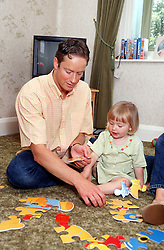 Father sitting on living room floor doing jigsaw puzzle with young daughter,