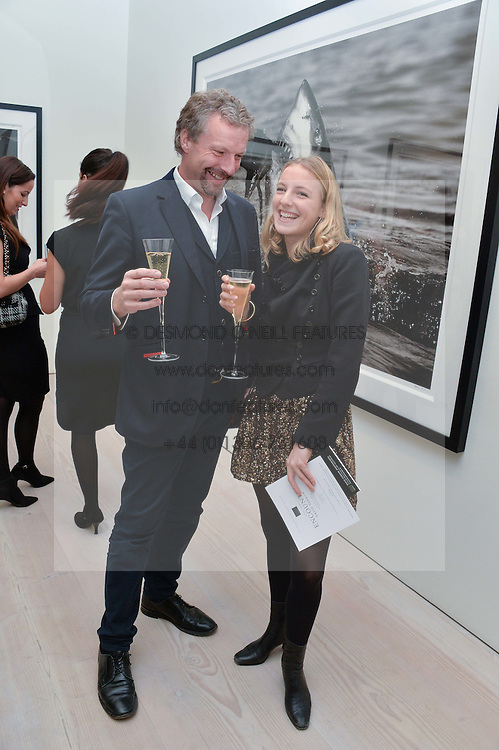 HUGO BURNAND and his daughter UNA BURNAND at a private view of photographs by wildlife photographer David Yarrow included in his book 'Encounter' held at The Saatchi Gallery, Duke of York's HQ, King's Road, London on 13th November 2013.