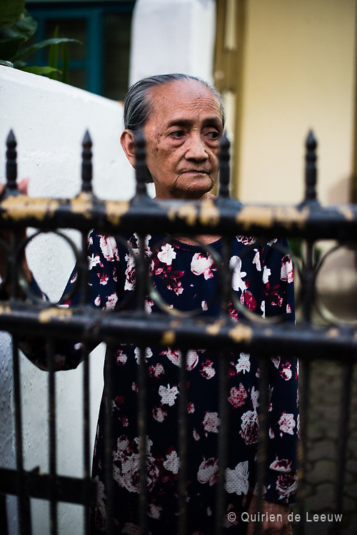 An old lady is standing in front of here house in a suburb of Bandung