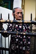 Een oude Javaanse vrouw aan het hek van haar huis in de voormalig koloniale stad Bandung.