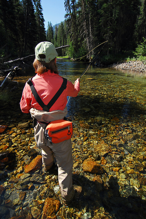 Woman fly fishing in the Lostine River, Northeast Oregon.