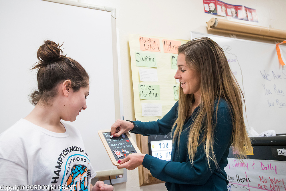Cara Nelson, right, a seventh grade social studies teacher at East Hampton Middle School, is presented with a present from seventh grader Olivia Masone, 12, upon returning from her recent trip that involved running seven marathons in seven days on seven continents, in East Hampton, Feb. 7, 2018. This was Nelson's first day back to school after finishing her last marathon on Monday in Miami.