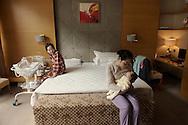 Shanghai, 21 septembre 2012.A la clinique  VIP Care Bay specialisee dans les soins post-natals, dans sa chambre, la jeune maman Bonnie Xu, observe alors que son infirmière dediee, Lu Yan, prends dans ses bras son fils nouveau-ne, Hehe.