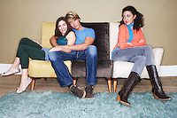 Third wheel sitting arms crossed on opposite end of sofa of hugging couple