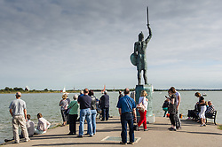 People gathering underneath the statue of Byrntnoth on the promenade at Maldon on the Blackwater River in Essex.