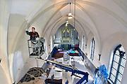 Nederland, Kekerdom, 9-2-2018De kerk die binnendijks ligt en een rijksmonument, krijgt een schilderbeurt . De heiligenbeelden zijn even van hun plaats gehaald en in een hoek gezet . Deze kerk staat deels op fundamenten van een 13e eeuws kerkje .Foto: Flip Franssen