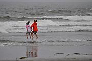 Girls jumping over waves, Washington Coast