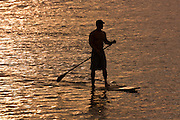 Stand-up paddleboarder at sunset in Hawaii