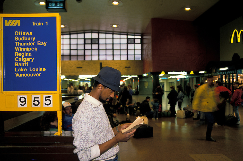 Canada, Quebec, Passenger Gary Johnson reads book while waiting for VIA Rail train in Montreal's Gare Central Station