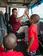 Houston ISD bus driver Reed Johnson poses for a photograph with students, July 16, 2014.