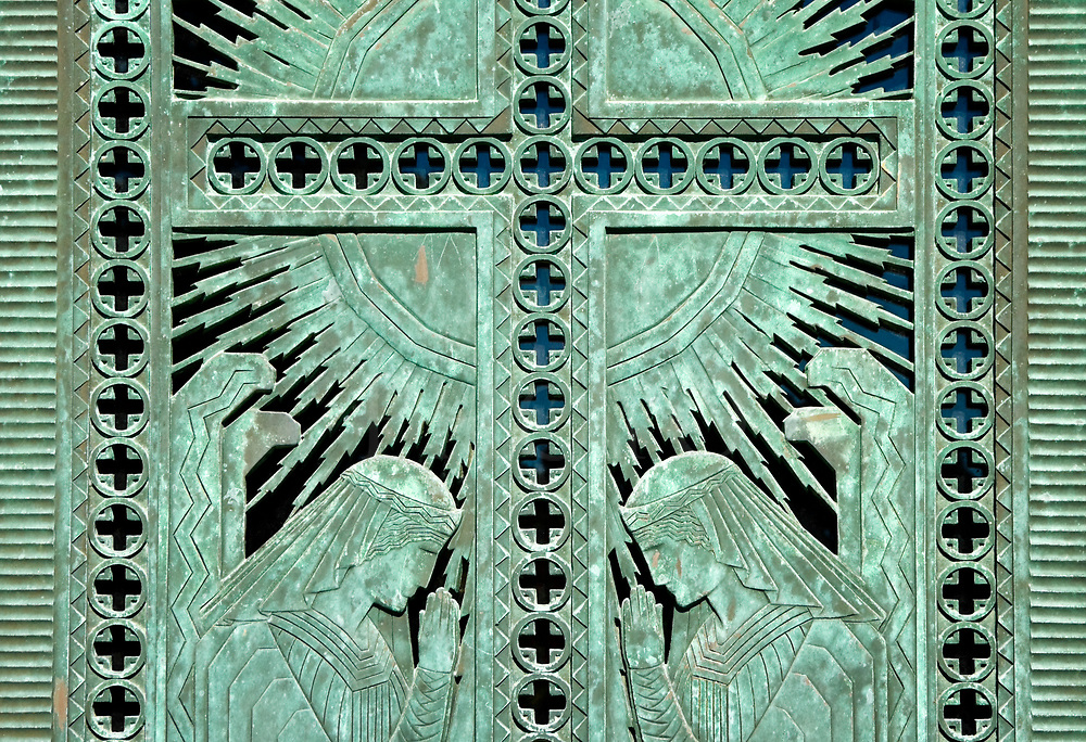 Praying angels in sculpted bronze mausoleum doors, worn and weathered by time into a beautiful green patina.