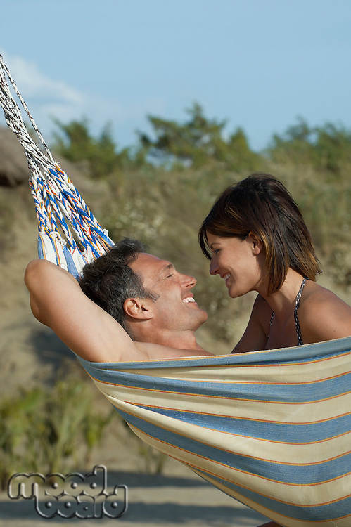 Couple in hammock laughing profile