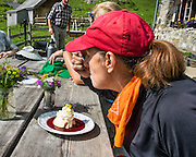 "Hikers enjoy delicious freshly-farmed panna cotta with raspberry sauce served at remote Widderalp mountain restaurant, in the Alpstein limestone range, Appenzell Alps, Switzerland, Europe. Himbeer is German for raspberry. Panna cotta (Italian for ""cooked cream"") is a dessert of sweetened cream thickened with gelatin and molded. The cream may be aromatized with rum, coffee, vanilla, or other flavorings. Located below Bötzel pass and accessible only to hikers, Widderalp comforts hikers with a homey restaurant and dormitory style (Matratzenlager) lodging. Appenzell Innerrhoden is Switzerland's most traditional and smallest-population canton (second smallest by area). For licensing options, please inquire."