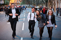 © Licensed to London News Pictures.  01/05/2015. OXFORD, UK. Students walk across Magdalen Bridge in Oxford on May Morning. Each year at 6am the Magdalen College Choir performs the Hymnus Eucharisticus, from the top of Magdalen Tower, a tradition dating back over 500 years. Around 6,000 students and local residents, some of who have stayed up all night, gather in the street below to listen.  Photo credit: Cliff Hide/LNP