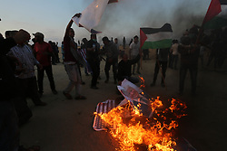 Palestinian Protesters burn an American flag and  pictures of US President Donald Trump  and shout slogans at the border fence with Israel east of Khan Yunis in the southern Gaza Strip, Israeli soldiers killed at least 60 Palestinians and wounded more than 2,700. as demonstrations on the Gaza-Israel border coincided with the controversial opening of the U.S. Embassy in Jerusalem. This marks the deadliest day of violence in Gaza since 2014. Gaza's Hamas rulers have vowed that the marches will continue until the decade-old Israeli blockade of the territory is lifted. Gaza Strip, Palestine, May 15, 2018. Photo by Ashraf Amra/SalamPix/ABACAPRESS.COM