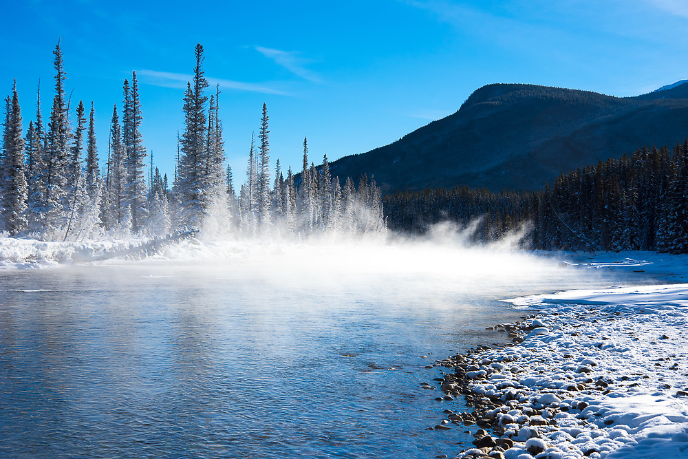 Great clouds of mist rise like smoke over the Bow River on a bitingly cold winter morning in Alberta's Banff National Park, the first established national park in Canada, and third in the world.