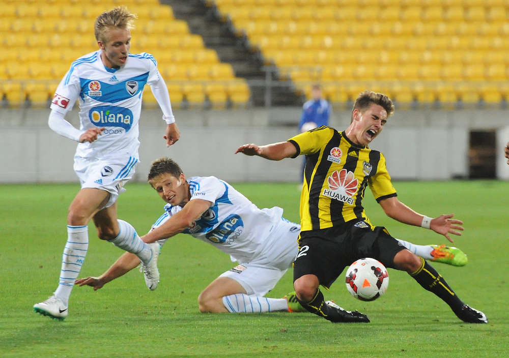 Phoenix's Tyler Boyd is taken down in against  Melbourne Victory FC tackle in the A-League football match at Westpac Stadium, Wellington, New Zealand, Saturday, Januray 18, 2014. Credit:SNPA / Ross Setford