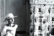 Mannequin in hat next to antique curtain