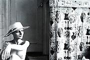 Mannequin in hat next to antique curtain