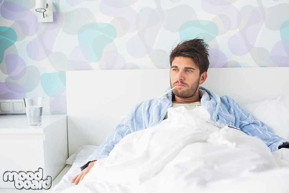 Sick man with thermometer in mouth reclining on bed at home