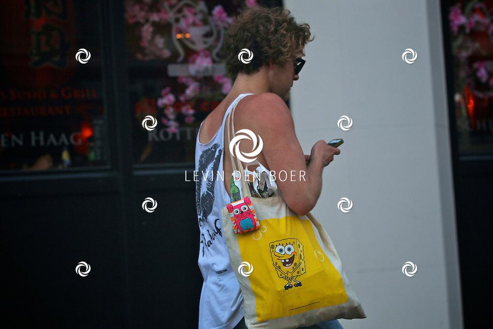 AMSTERDAM - Paul Turner aan het wandelen midden in Amsterdam met zijn mobiel in zijn handen. FOTO LEVIN DEN BOER