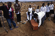 A three-year-old victim of AIDS is buried by her family in the unending cemetary emerging around Lusaka, Zambia.
