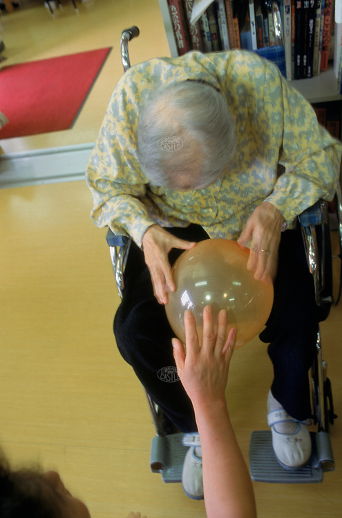 Original caption: Tokyo, Japan:  Shisei home for the aged and senior day care center; balloon catch with resident to help with coordination. August 1998 Tokyo, Honshu, Japan