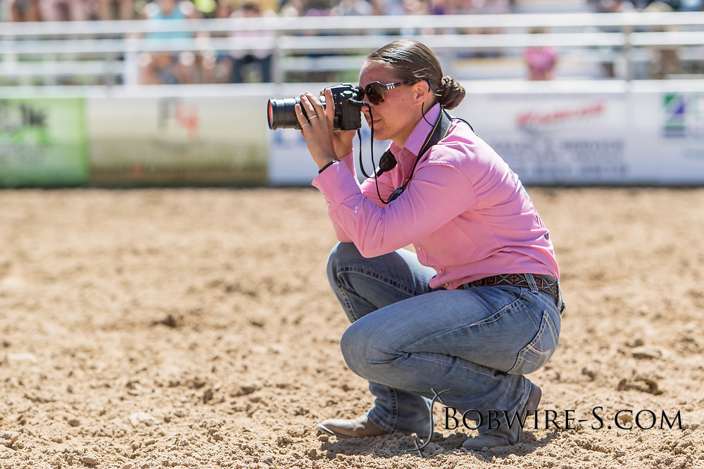 A member of the U.S. Marine Corps Mounted Color Guard takes photos of Mutton Bustin' in the first performance of the Elizabeth Stampede on Saturday, June 2, 2018.