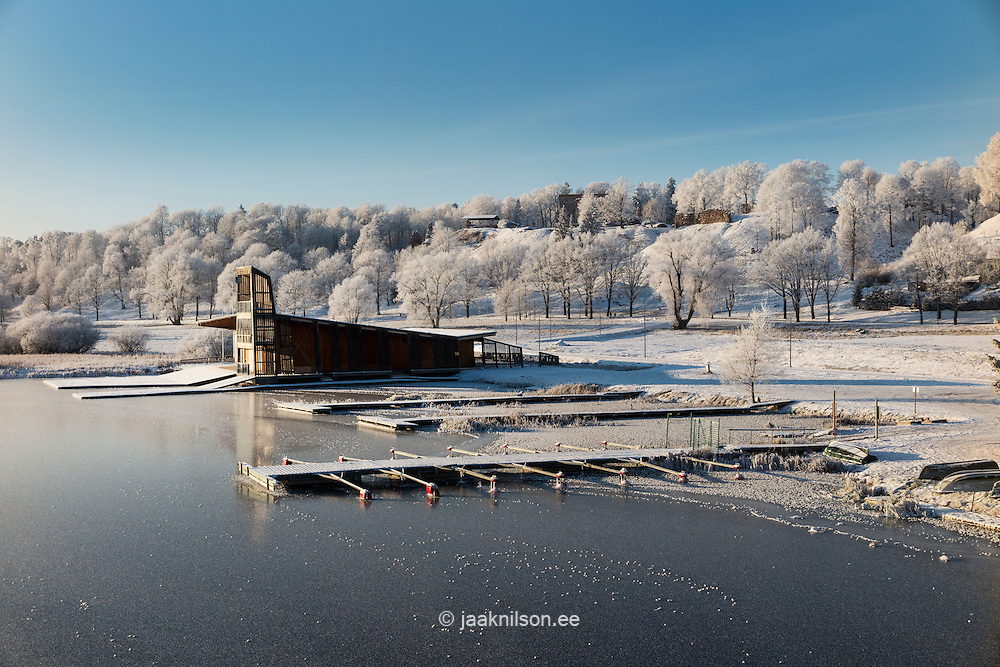 Wooden floating boardwalk covered snow. Viljandi lake in Estonia. Waterfront, beach and rest area at winter.