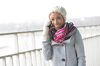 Happy woman in winter wear using cell phone outdoors