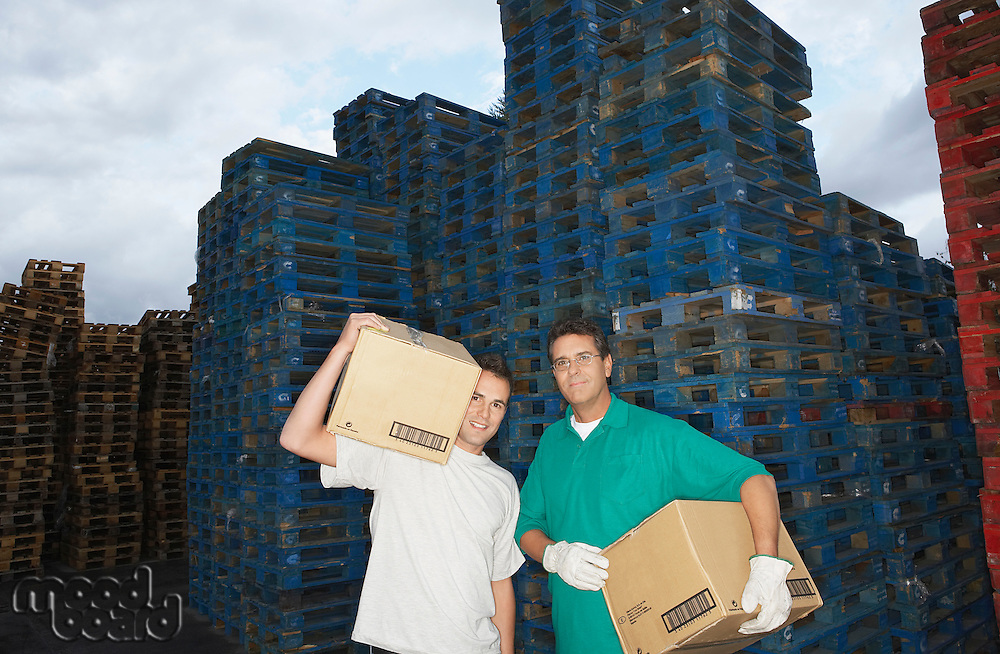 Warehouse Workers Carrying Boxes in front of stacks of pallets