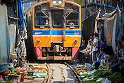17 JANUARY 2013 - SAMUT SONGKHRAM, SAMUT SONGKHRAM, THAILAND: A train pulls into the market in Samut Songkhram. Four trains each day make the round trip from Baan Laem, near Samut Sakhon, to Samut Songkhram, the train chugs through market eight times a day (coming and going). Each time market vendors pick up their merchandise and clear the track for the train, only to set up again when the train passes. The market on the train tracks has become a tourist attraction in this part of Thailand and many tourists stop to see the train on their way to or from the floating market in Damnoen Saduak.    PHOTO BY JACK KURTZ