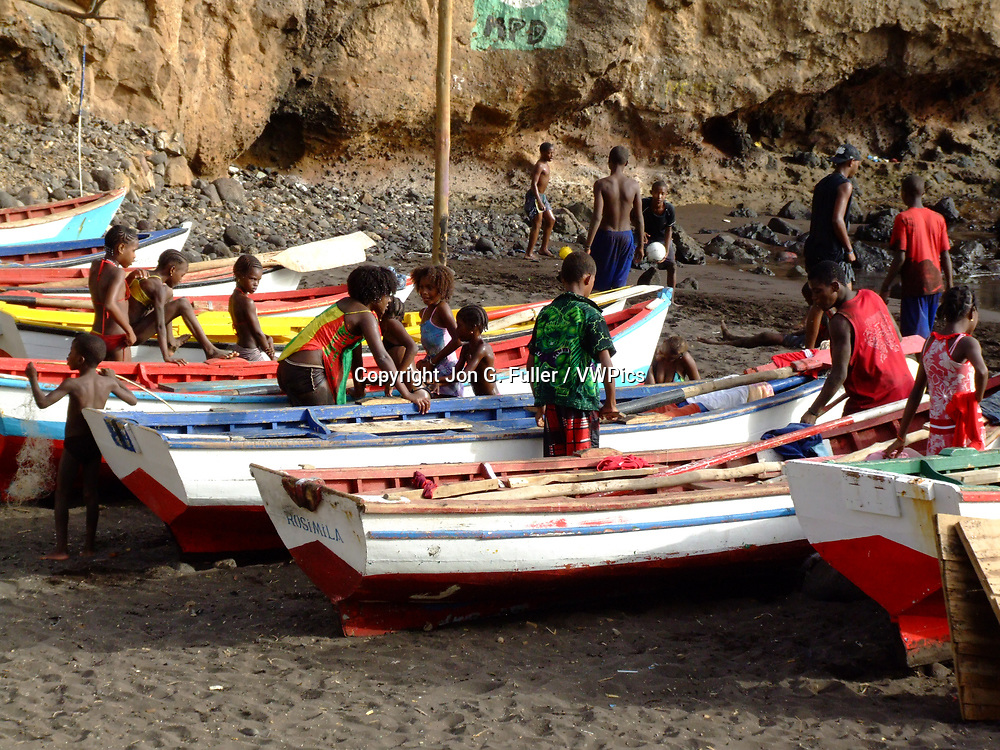 Children play on colorful fishing boats on shore in Cidade Velha on the island of Santiago, Cabo Verde or Cape Verde.