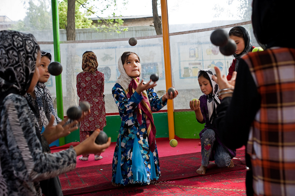 A young Afgan girl juggles balls during practice in the Afghan Mobile Circus School. Kabul, Afghanistan, 2012