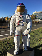 Garden City, New York, USA. October 23, 2015. When New York METS clinch a trip to the World Series, the NASA astronaut statue at entrance to Long Island Cradle of Aviation Museum looks like big METS fan, wearing blue and orange Mets cap and holding large plastic baseball. On October 19, the Mets completed their sweep against Chicago Cubs in the National League Championship Series.