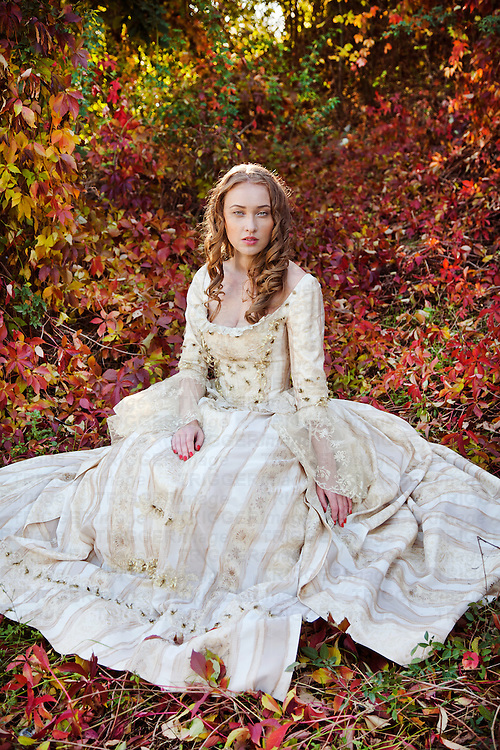 Young blonde woman wearing a period costume sitting alone outdoors in woodland with red autumn leaves