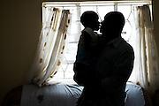 Nairobi, Kenya -   2015-03-31  -  Grace Wambui, 6, gets a kiss from her father Geoffrey Mwangi at home in Nairobi, Kenya on March 31, 2015.  Photo by Daniel Hayduk