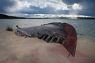 A wrecked boat sits beached in Munising Bay as an autumn storm passes over.