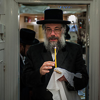 London, UK - 13 April 2014: Rabbi Osher Schapiro of the Jewish Community of Stamford Hill searches for chametz (leavened bread products) in his house on the night before Passover.