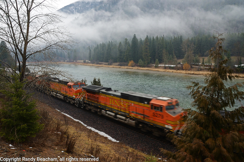 A BNSF train traveling by the Kootenai River during a rainstorm in winter. Near Libby in Lincoln County, northwest Montana.