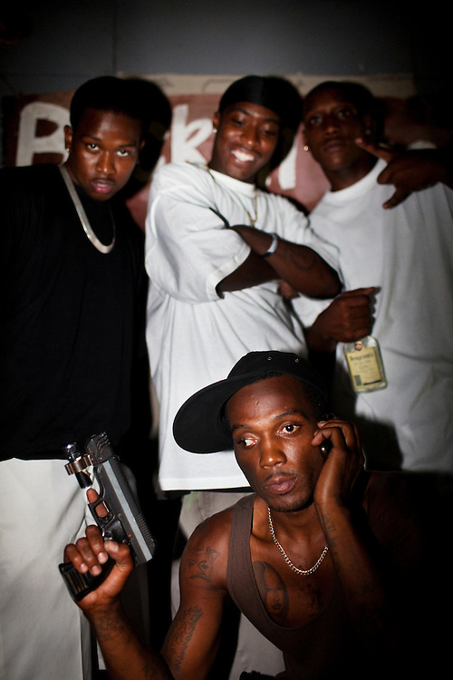 "Winky Williams (front) Demetris ""Butta"" Anderson (back L), Martez Maggitt (back center) and another friend mug for the camera during another late night of drinking, selling drugs, gambling and talking shit on the corner in the Baptist Town neighborhood of Greenwood, Mississippi on Saturday, July 3, 2010. Since this image was made Winky moved to Texas to start a new life but was arrested and sent back, Butta was shot and killed, and Martez  was sent to prison."