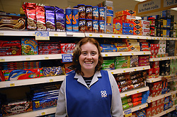 Portrait of shop assistant with learning disability standing in front of shelves of biscuits in supermarket smiling,