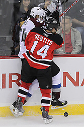 Oct 15; Newark, NJ, USA; New Jersey Devils center Tim Sestito (14) hits Colorado Avalanche right wing David Jones (54) during the third period at the Prudential Center. The Avalanche defeated the Devils 3-2.