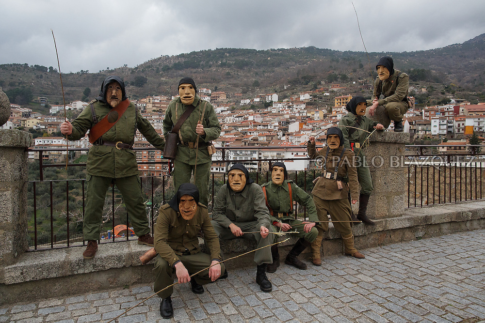 The Machurreros from Pedro Bernardo pose for a picture at a park during Carnival on February 6, 2016 in Pedro Bernardo, in Avila province, Spain. The origins of this pagan festival are unknown. The Machurreros wear wood masks, a military dress, black handkerchief, cowbells, and hold wicker stick. The festival disappeared after Dictator Franco forbid carnival festivals in 1937, but it was recently recovered. Before disappearing, male villagers after the military service, used to dress as Machurreros as they run along the streets scaring children and adults with their wicker stick to bring fertility to the land and expel the evil spirits. (© Pablo Blazquez)