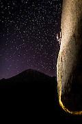 Against a dark sea of stars, Aaron Livingston solos the Southwest Arete, 5.9. <br /> The Buttermilks, California