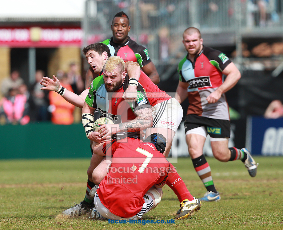 Picture by Paul Terry/Focus Images Ltd +44 7545 642257.07/04/2013.Joe Marler ( C ) of Harlequins is tackled by Tommy O'Donnell ( 7 ) and James Downey of Munster during the Heineken Cup match at Twickenham Stoop , London.