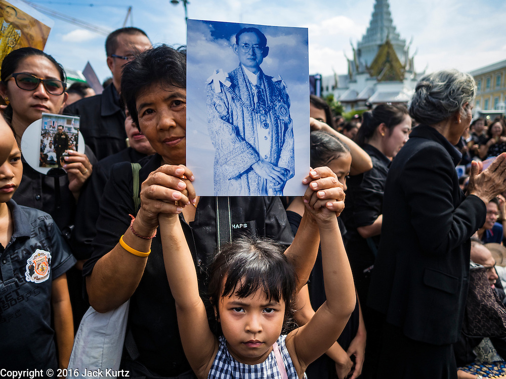 22 OCTOBER 2016 - BANGKOK, THAILAND: A woman and her daughter hold up a portrait of the late Bhumibol Adulyadej, the King of Thailand, during the singing of the King's Anthem on Sanam Luang Saturday. Sanam Luang, the Royal Ceremonial Ground, was packed Saturday with more than 100,000 people mourning the Monarch's death. The King died Oct. 13, 2016. He was 88. His death came after a period of failing health. Bhumibol Adulyadej was born in Cambridge, MA, on 5 December 1927. He was the ninth monarch of Thailand from the Chakri Dynasty and is also known as Rama IX. He became King on June 9, 1946 and served as King of Thailand for 70 years, 126 days. He was, at the time of his death, the world's longest-serving head of state and the longest-reigning monarch in Thai history.        PHOTO BY JACK KURTZ