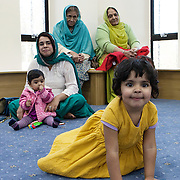 Slough, Greater London, UK, January 24, 2015. Ramgharia Sikh Gurdwara Temple.<br /> A young woman, pregnant for the third time, with her two daughters, her mother in law and a relative.  This woman came from India to be married in the UK and live with her in-laws. Low value of girls, son-preference can still be found in the Indian community. Often isolated, these Indian wives can  sometimes become victims of pressures to produce a boy, even in the UK.