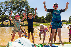 Cousins, left to right, Scarlet, 7, Charlie, 6, Poppie, 3 and Frankie, 10 have plenty to cheer about at Beckenham Place. With temperatures soaring into the 30s hundreds take advantage of the hot weather and London's newest wild swimming lido at Beckenham Place in South East London. London, July 23 2019.