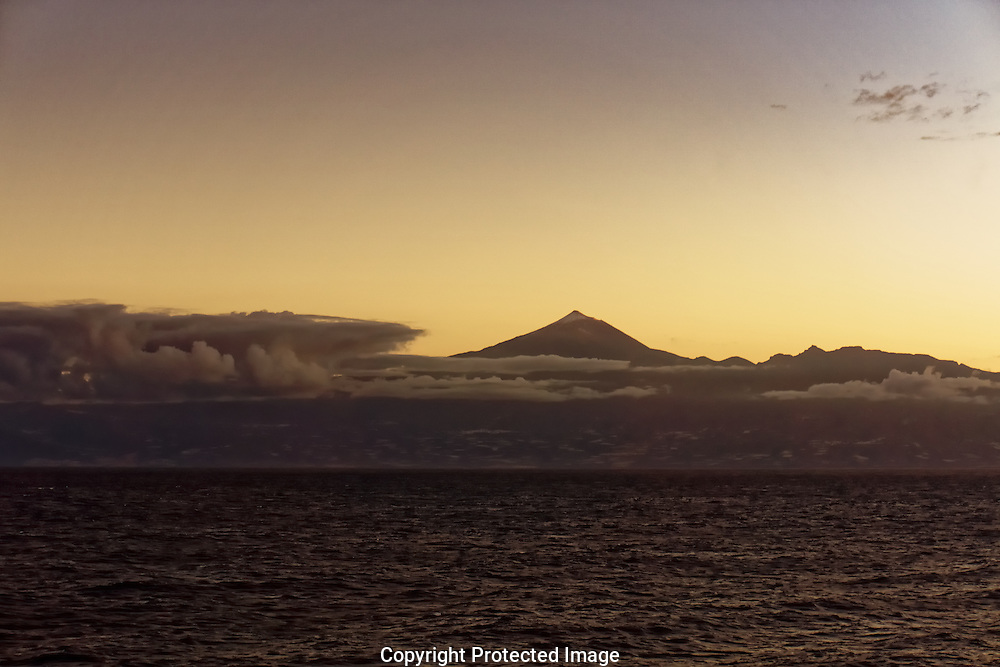 Mount Teide, the world's third largest volcano,  peaking above dawn clouds from the sea off Tenerife, in the Canary Islands.